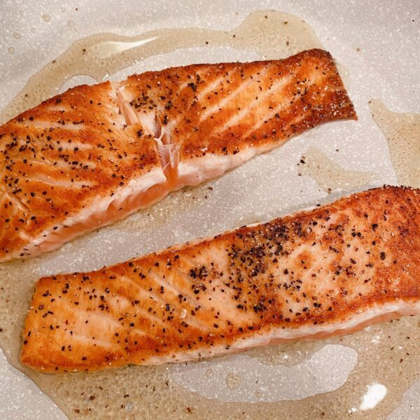 Salmon searing in the skillet on top of the stove