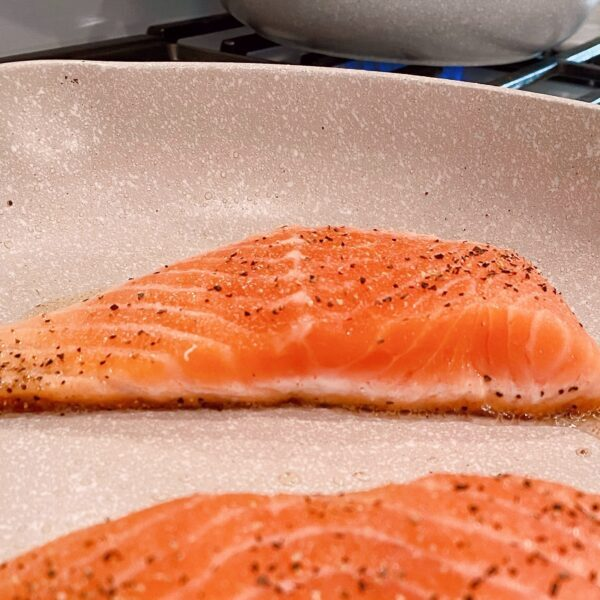 Salmon cooking in the skillet.