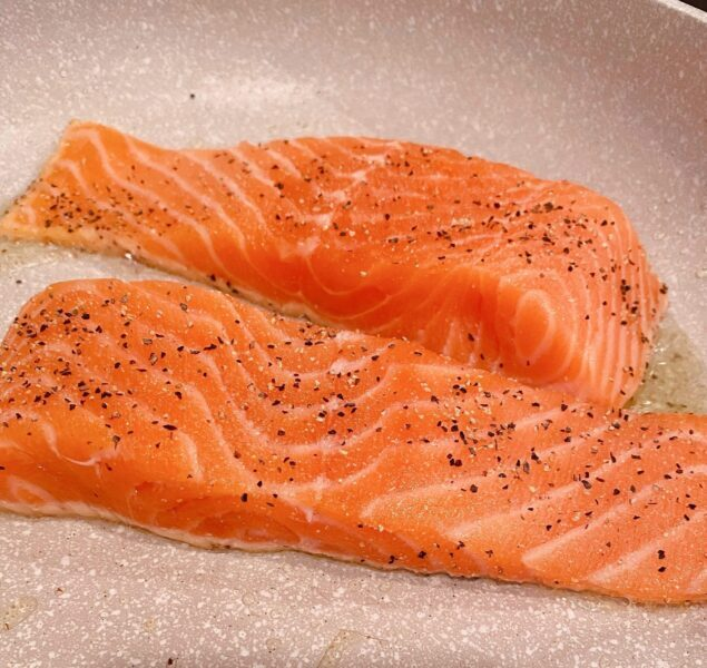 Salmon in skillet with hot olive oil