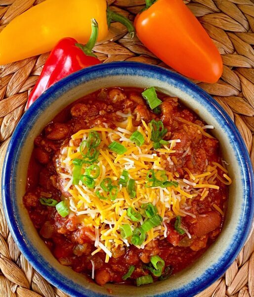 Bowl full of slow cooker chili with grated cheese and onions.