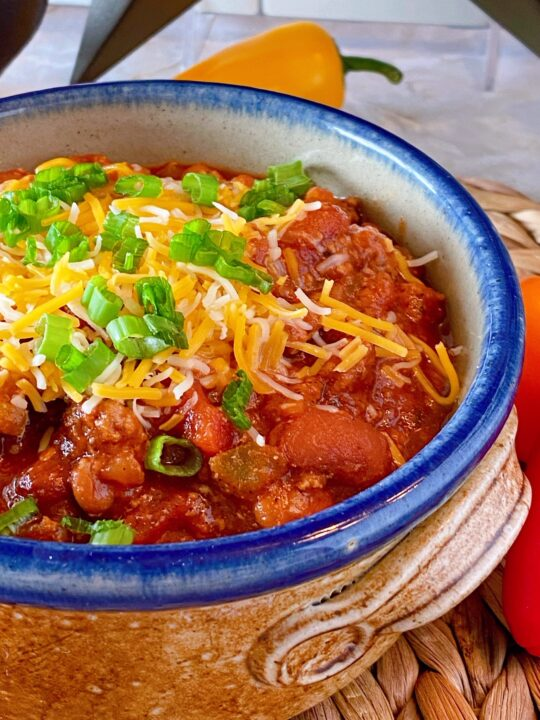 Slow Cooker Chili in a rustic ceramic bowl with cheese and green onions