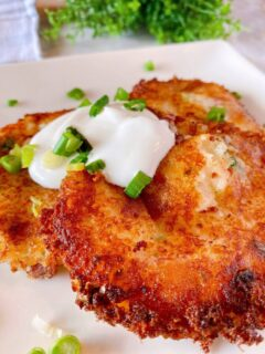 Loaded Mashed Potato Cakes on a plate with sour cream and chives