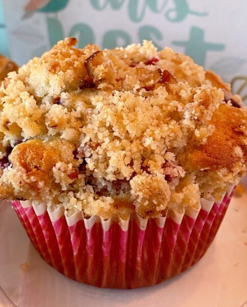 close up photo of one of the streusel topped mixed berry muffin.