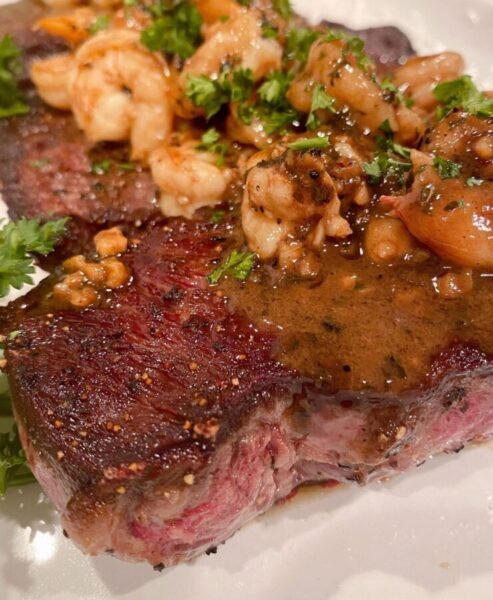 Wine sauce poured over the top of steaks and shrimp.