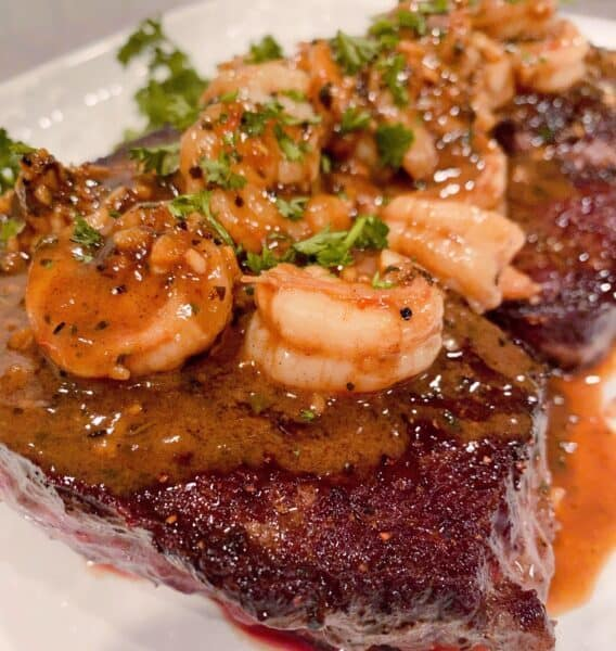 Denver Steaks on a platter with shrimp and red wine sauce