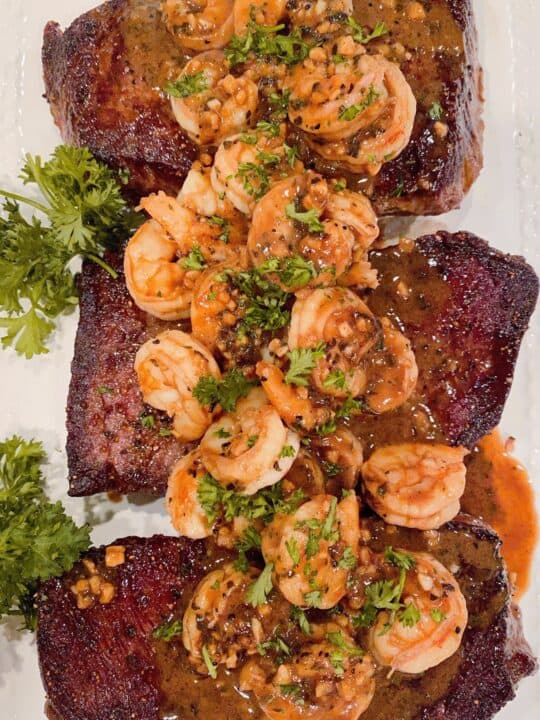 Denver Steaks with Shrimp and garlic herb sauce on a platter with parsley garnish