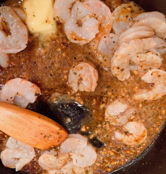 Adding garlic, butter and shrimp to hot skillet to cook the shrimp.