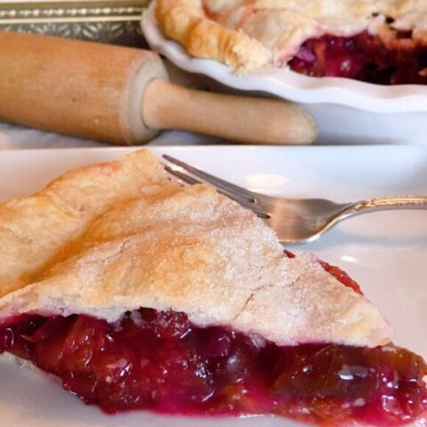 Big slice of Plum Pie with a fork ready to eat. Rolling Pin and Whole Plum Pie in the background