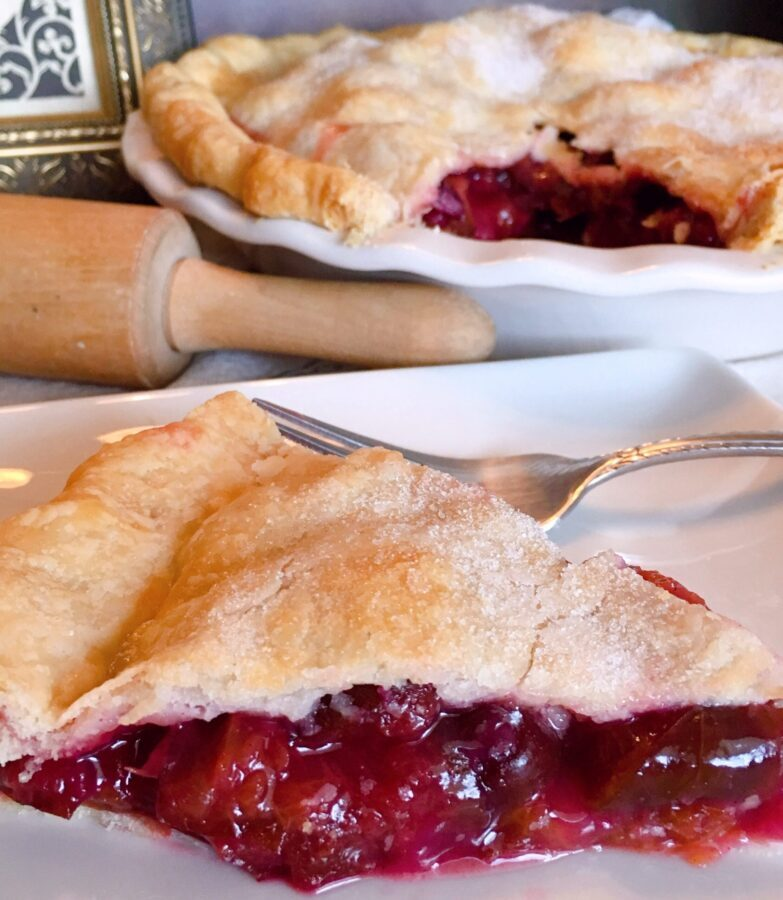 Slice of Plum Pie with whole pie in the background and a rolling pin on the kitchen counter