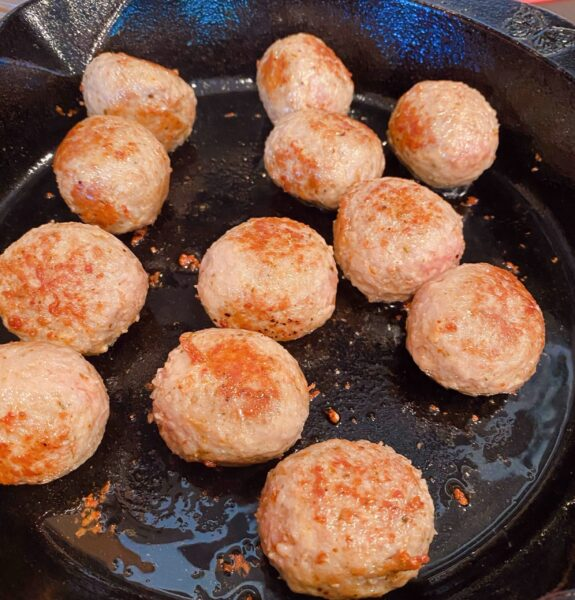 Large cast iron skillet on a stove top with browning meatballs.
