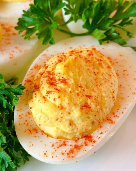 Close up of one deviled egg ready to eat.