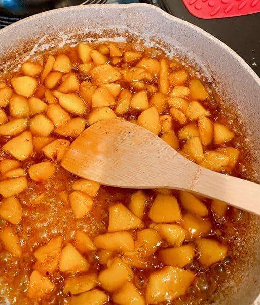 peaches frying in the skillet with brown sugar and spices.