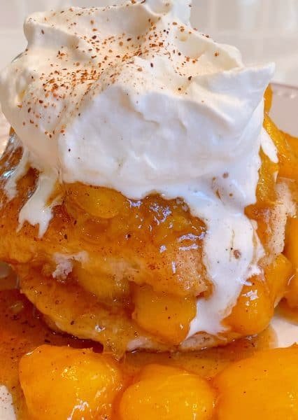 Fried Peaches and biscuit topped with whipping cream and nutmeg