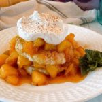 Fried Peach Sweet Biscuit Shortcakes on a plate with whipped cream and a sprig of mint