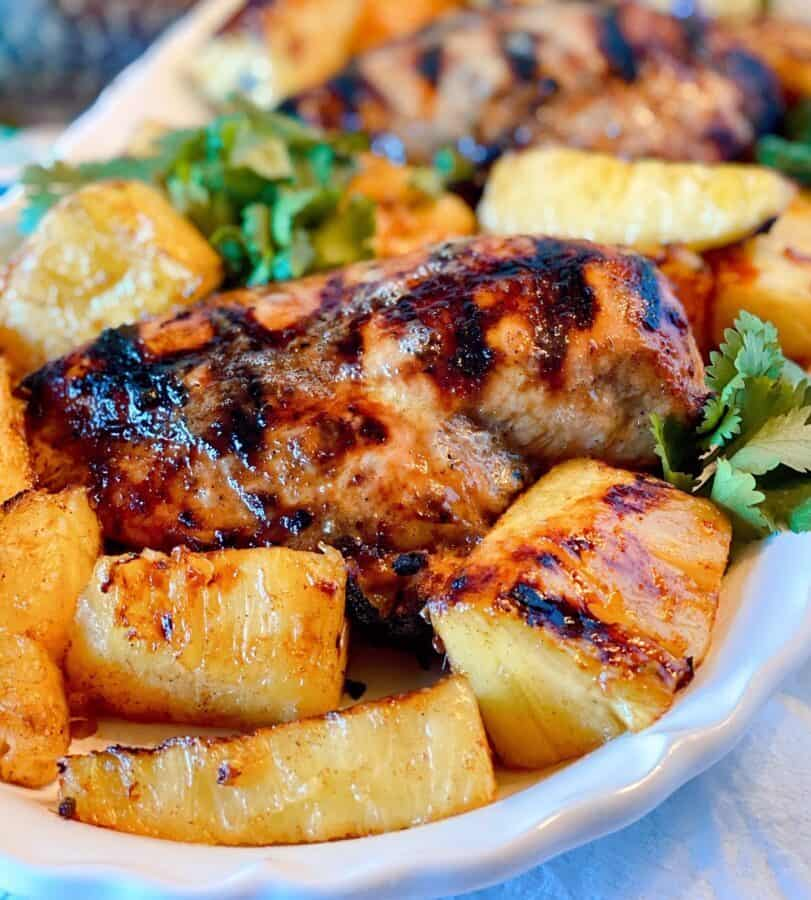 Close-up photo of a grilled jerk chicken breast on a white platter with grilled pineapple spears.