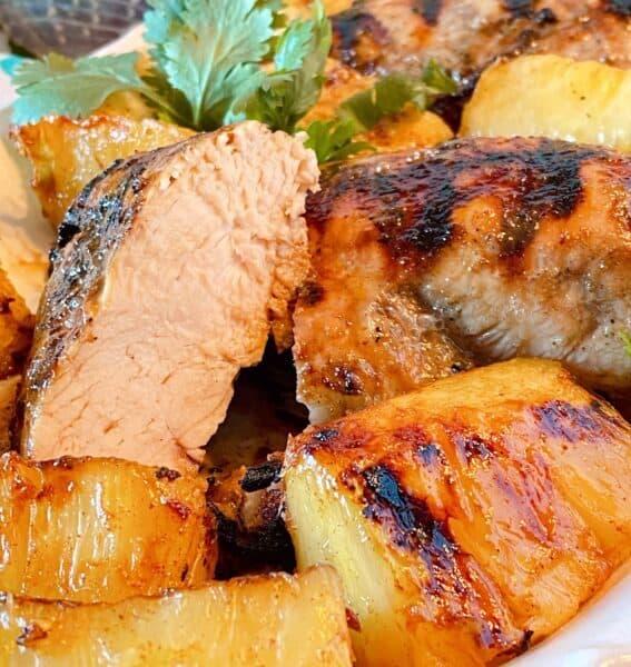 Chicken breast cut in half on the serving platter exposing tender juicy grilled chicken breasts.