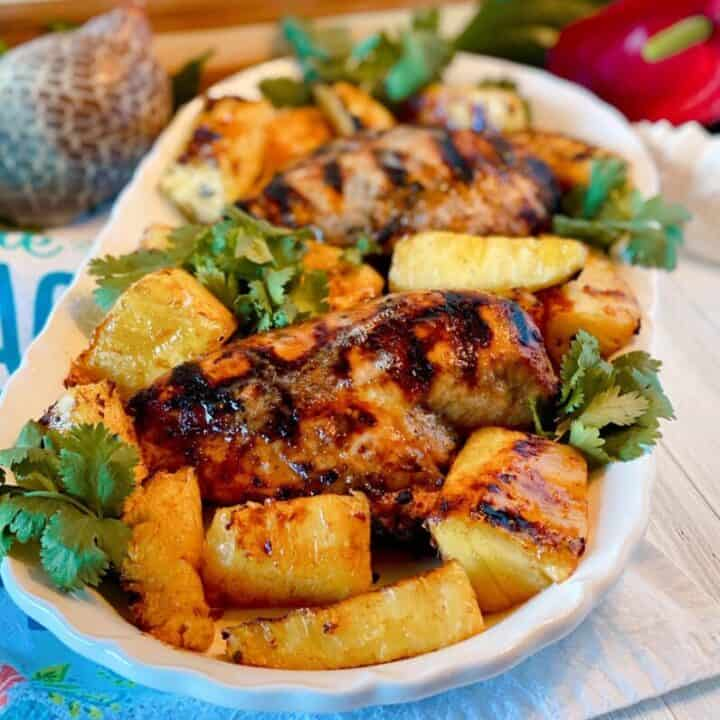 Platter filled with grilled jerk chicken breasts, grilled pineapple spears, and cilantro.
