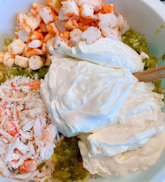 Adding Mayonnaise, sour cream, relish, and sugar to the salad mixture.
