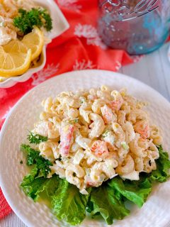 White plate with lettuce and a huge serving a Seafood Pasta Salad on a white board.