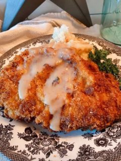 Chicken Fried Pork Steak on a plate with creamy gravy and mashed potatoes
