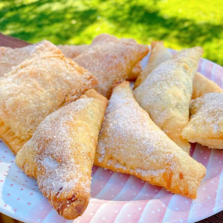 Plate filled with homemade fried peach hand pies coated in cinnamon sugar