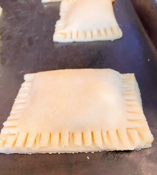 Fresh hand pie's made and ready to fry on a baking sheet.