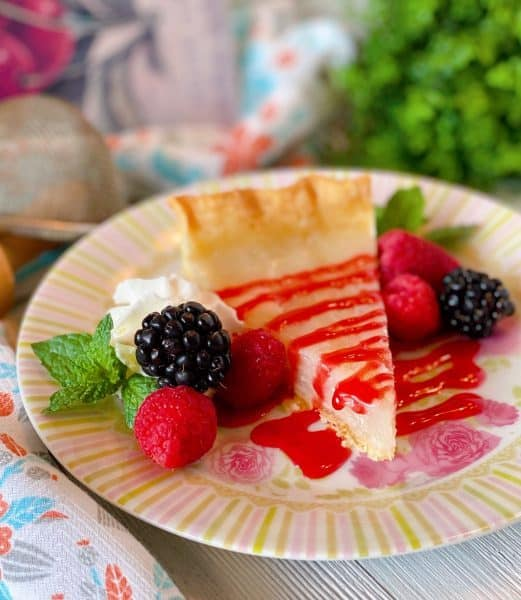 Slice of Water Pie with Raspberry sauce and fresh berries.