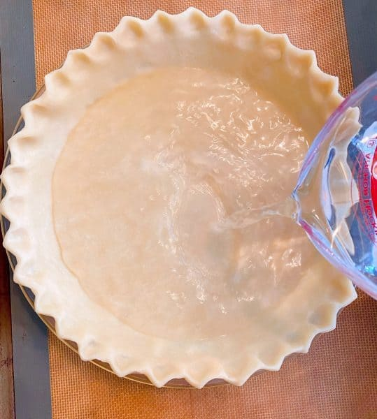 Pouring water into prepared pie crust.