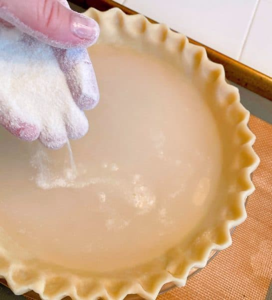 Sprinkling flour and sugar over the water in the pie crust