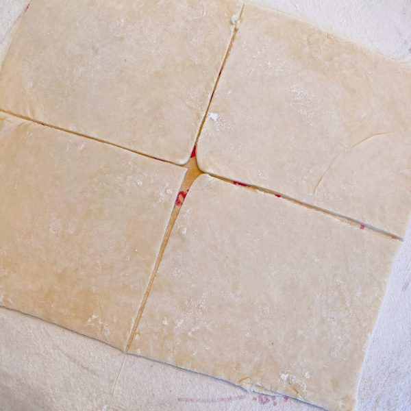 Pie dough cut into 4 equal 6 inch squares to wrap apples in for dumplings.