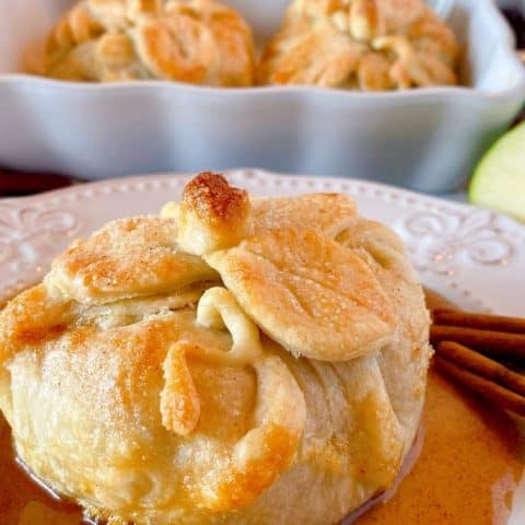 Country Apple Dumpling on a plate with a pool of cinnamon sauce and more apple dumplings in the background