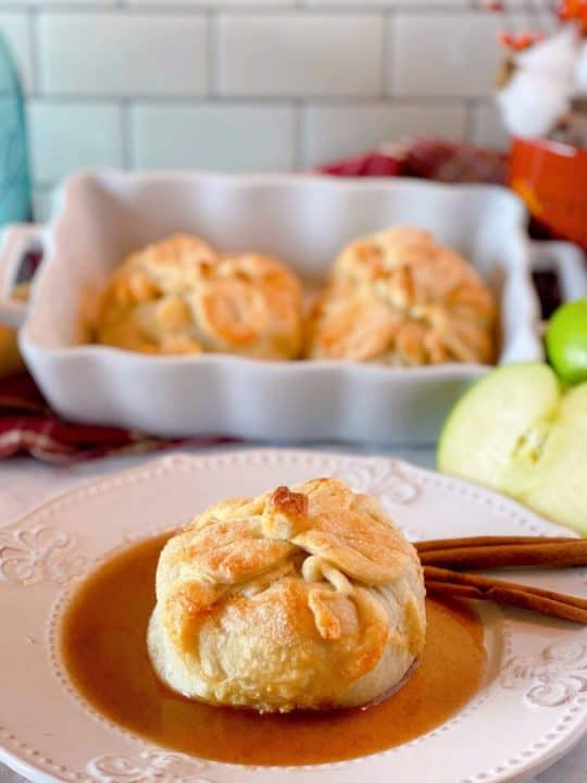 Country Apple Dumpling on a plate with cinnamon sauce and more apple dumplings in a baking dish in the background