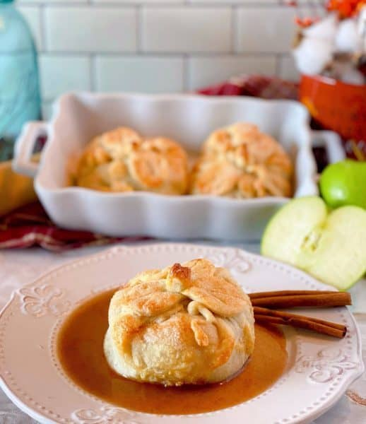 Apple Dumpling on a dessert plate with cinnamon sauce and more apple dumplings in the background