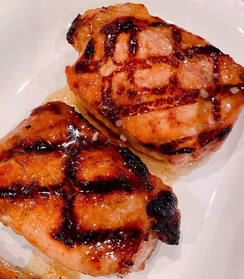 Two Grilled Brown Sugar Glazed Pork Chops on a white plate.