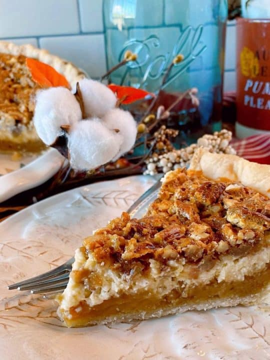 Slice of Caramel Pecan Cheesecake Pie on a tan plate with a fork and whole pie in the background with fall decor.