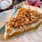 Close up of slice of Caramel Pecan Cheesecake Pie on a plate with a fork
