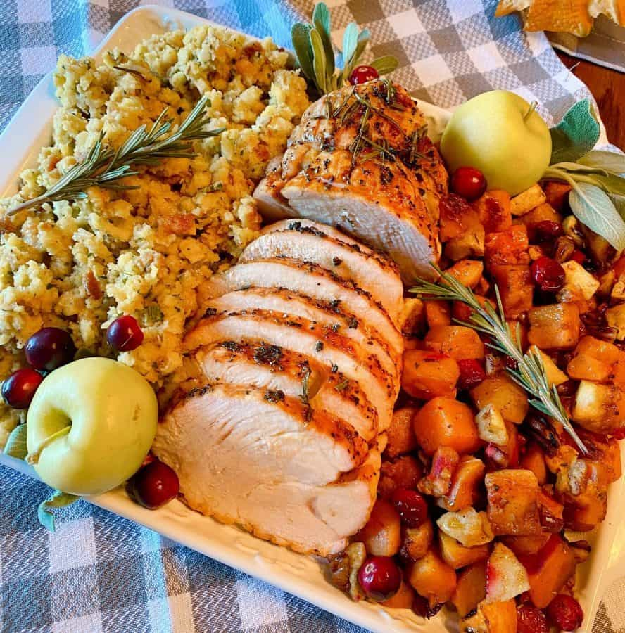 Herb Crusted Turkey Roast on a platter with roasted squash and stuffing.