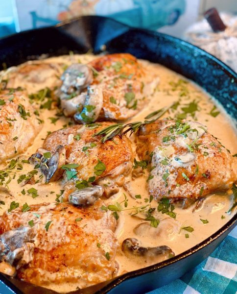 Chicken thighs fully cooked in wine mushroom sauce spooned over chicken