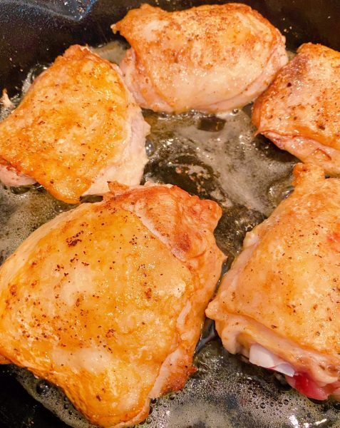 Golden Chicken Thighs frying in skillet.