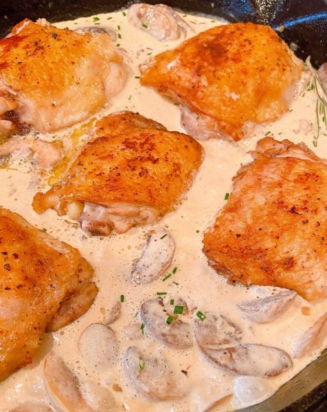 Adding chicken thighs back into herbed mushroom sauce.