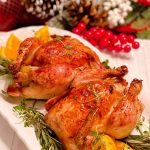 Roasted Cornish Game Hens on a platter with herbs