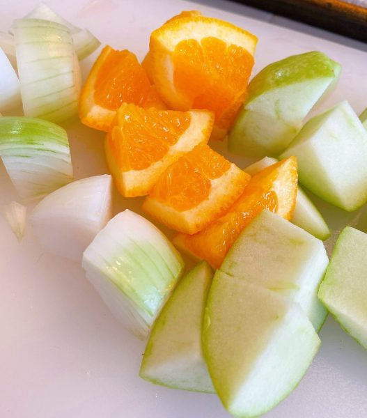 Orange, apple, and onion chunks on cutting board for stuffing hens