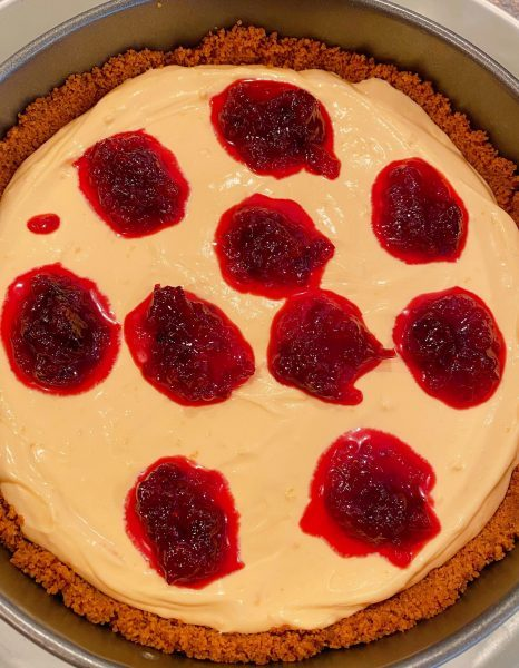 Dotting cheesecake with cranberry sauce
