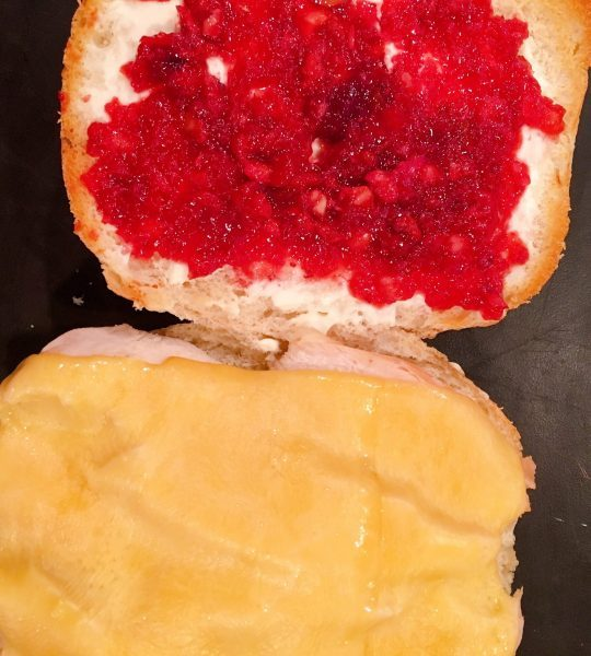 Turkey sandwich with melted gouda cheese adding cranberry sauce.