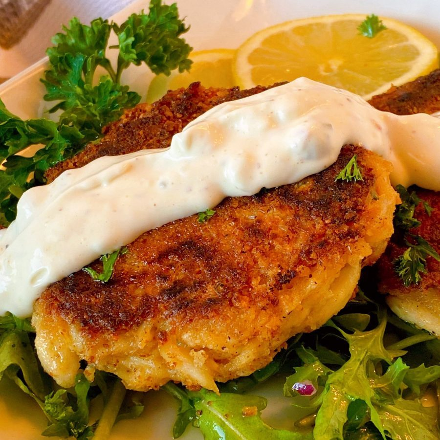 Lump Crab Cakes with homemade tartar sauce on a plate with arugala