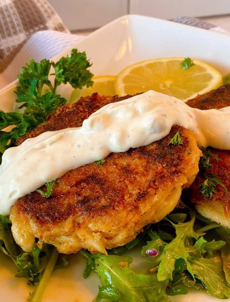 Crab cake with tartar sauce drizzled over the top