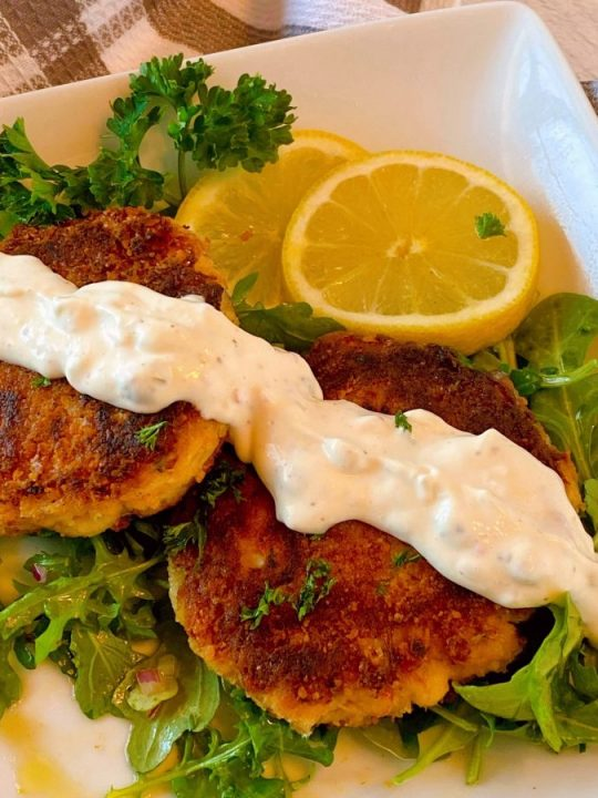 Lump Crab Cakes on a plate with homemade tartar sauce drizzled across the top.