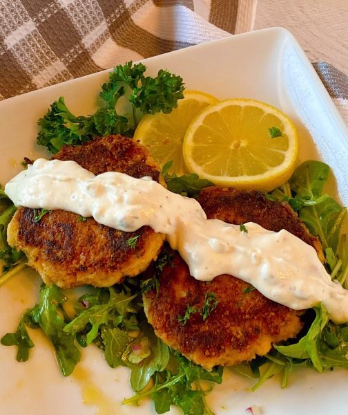 Crab Cakes with Tartar sauce and arugula salad on a plate