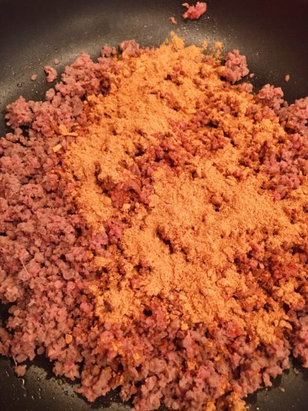 Browning Ground Beef and Taco seasoning in a large skillet over medium heat.