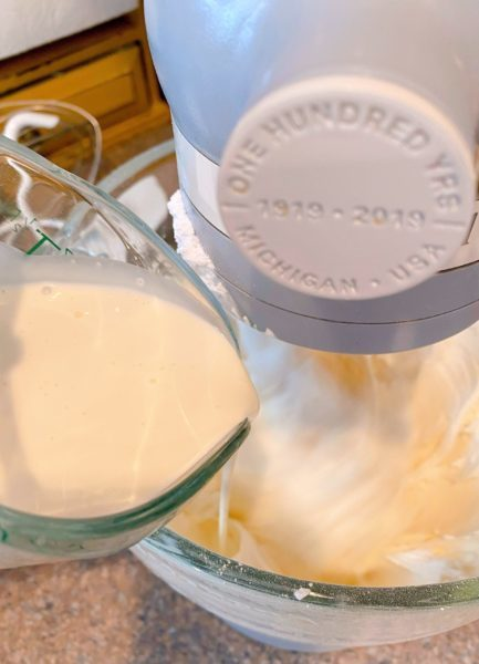 Adding whipping cream to buttercream mixture in the mixing bowl.
